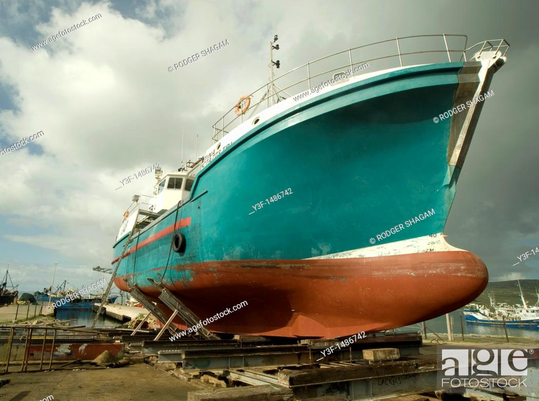 Stock Photo: A fishing trawler on the slipway being prepared for a new coat of paint.