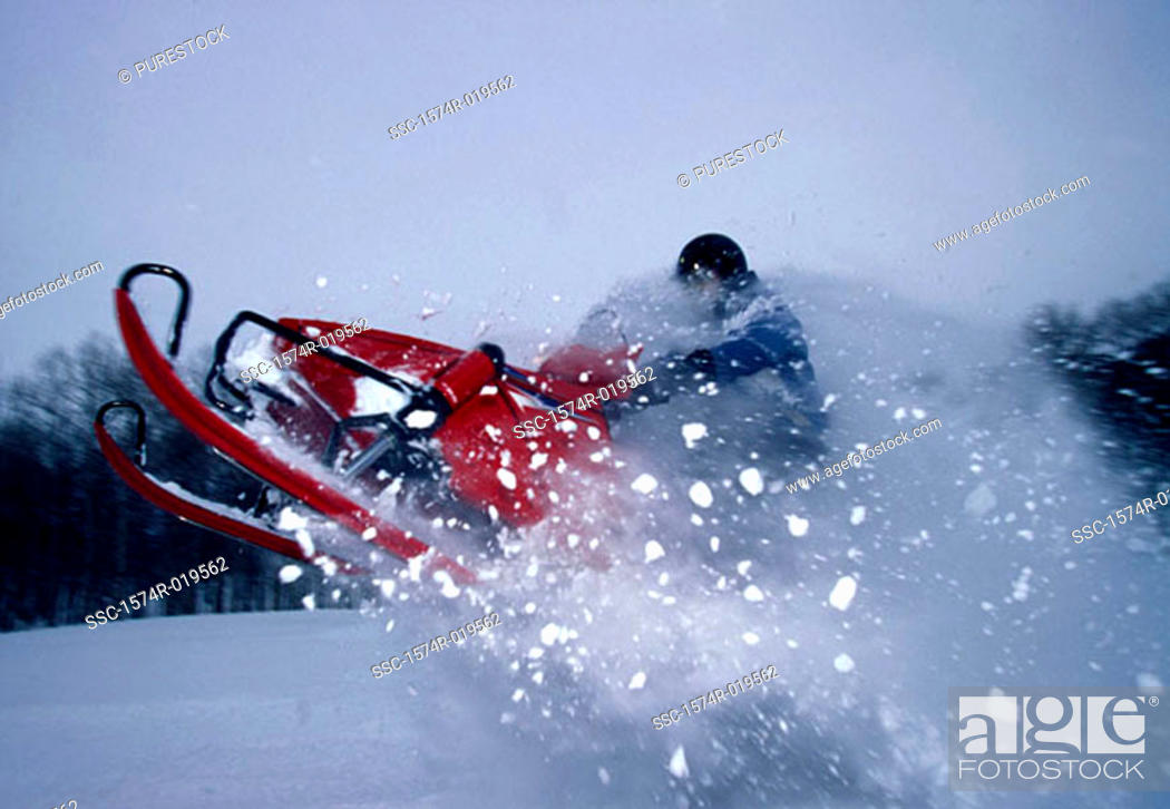 Stock Photo: Side profile of a man riding a snowmobile.