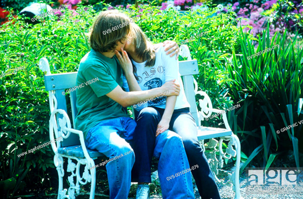 Stock Photo: Young couple sitting on a park bench kissing.