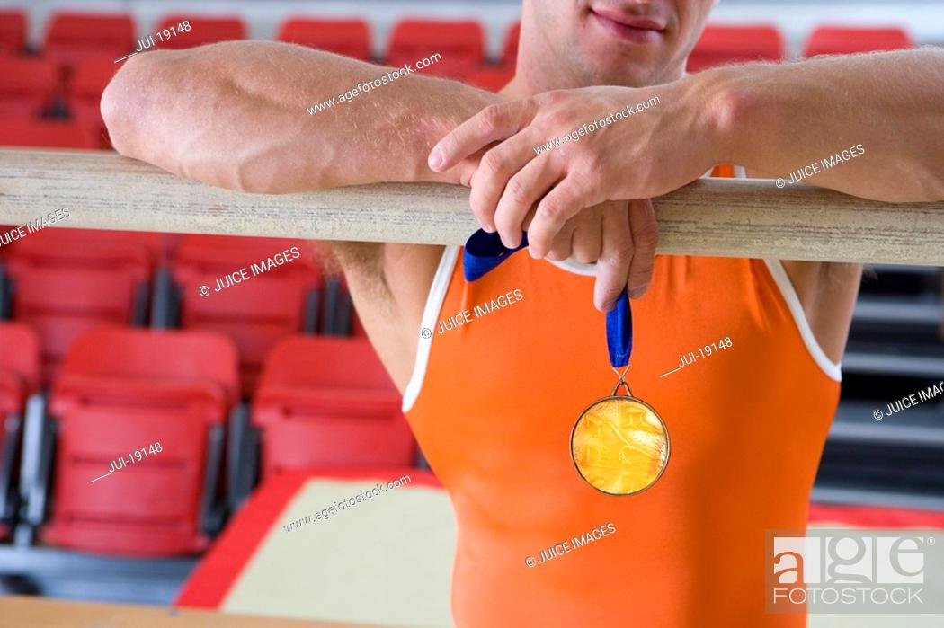 Stock Photo: Male gymnast with gold medal, arms on bar, mid section.