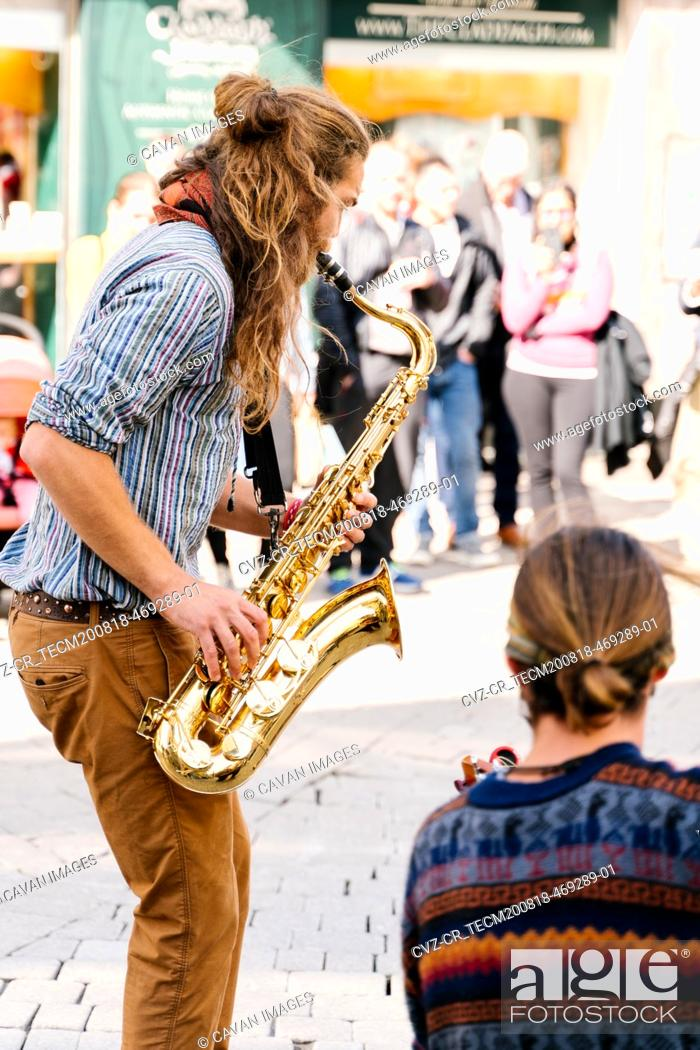 Stock Photo: Saxophone player on his back playing next to a guitarist on the street.