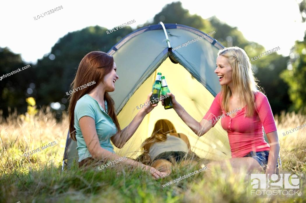 Stock Photo: Three young women camping, two drinking beers.