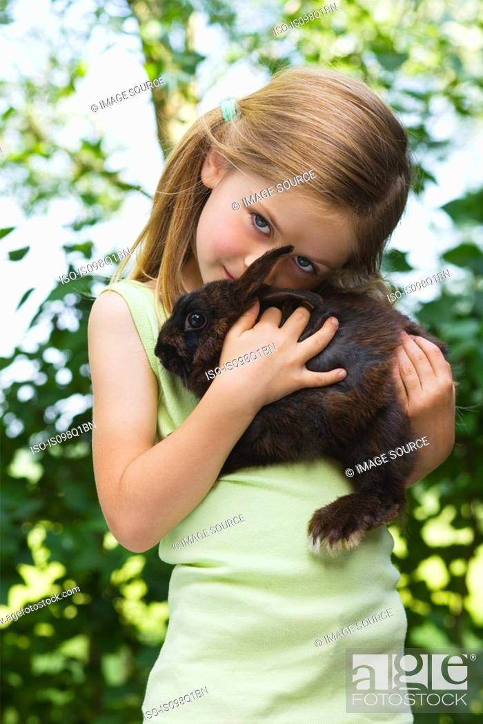 Stock Photo: Portrait of a girl holding a rabbit.