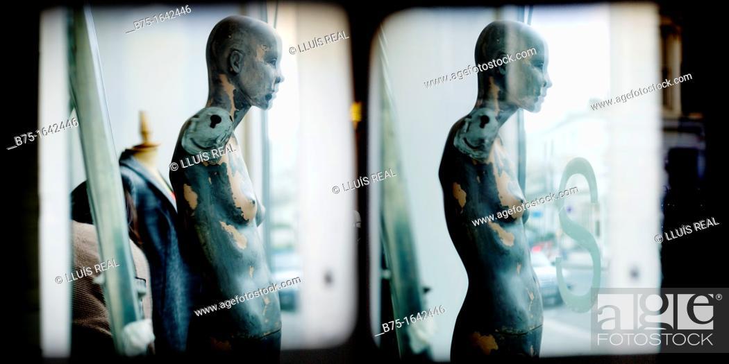 Stock Photo: Female mannequin in a shop window broken.
