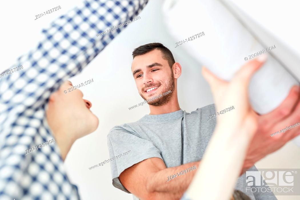 Imagen: Paar beim Tapezieren zusammen mit Tapete an Wand beim Renovieren von einer Wohnung.