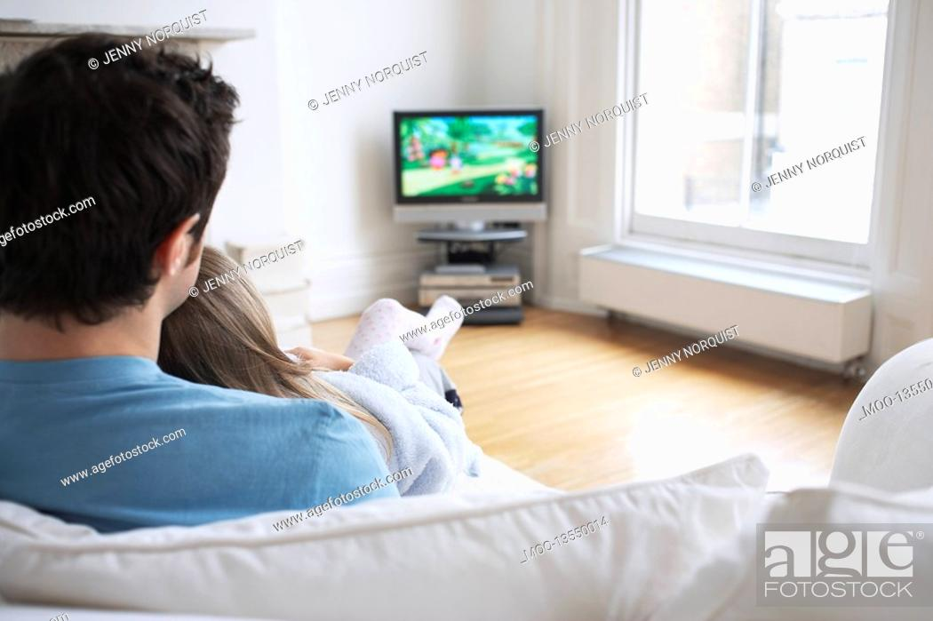 Stock Photo: Father and daughter 5-6 watching cartoons in television back view.