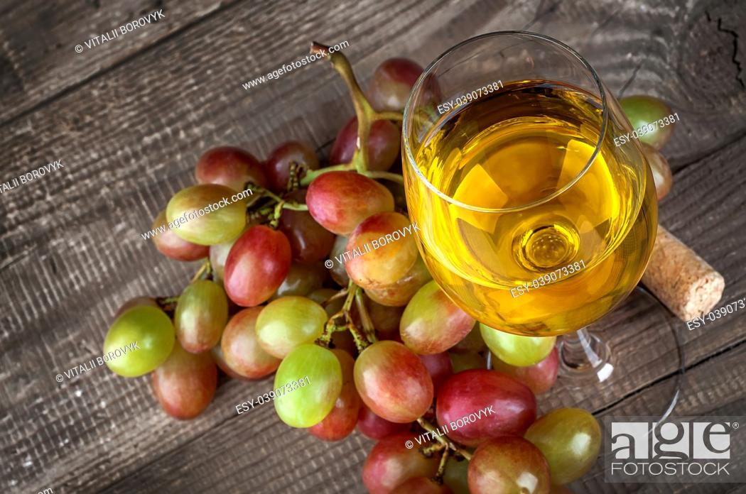 Stock Photo: Glass of white wine with a cluster of grapes on wooden table background, top view.