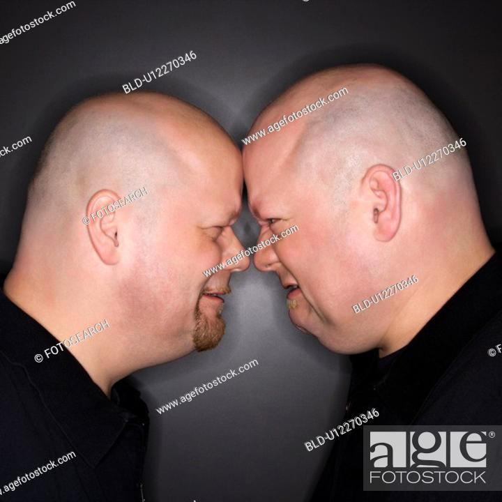 Stock Photo: Bald mid adult identical twin men standing face to face with angry expression.