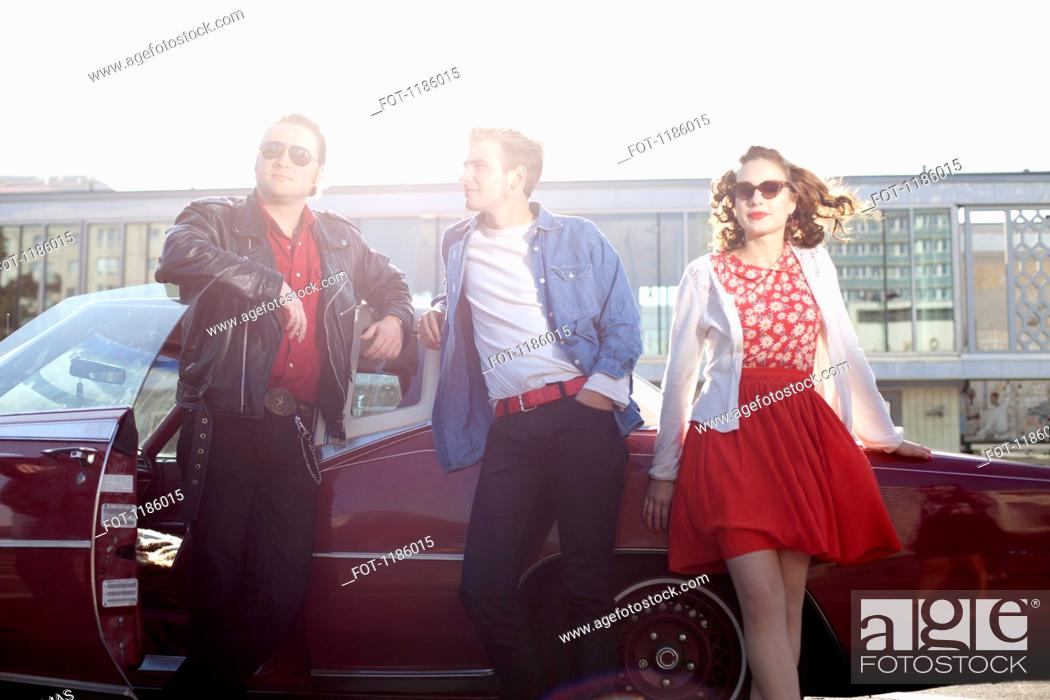 Stock Photo: Three rockabilly friends leaning against a vintage car.
