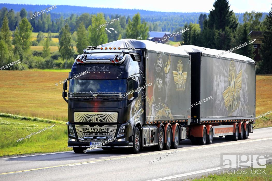 Stock Photo: JAMSA, FINLAND - AUGUST 23, 2018: The spectacular show truck Volvo FH16 Ace of Spades transports load on scenic road in Central Finland in late summer.