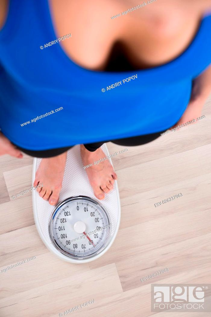 Stock Photo: High Angle View Of Woman Measuring Body Weight On Weighing Scale.