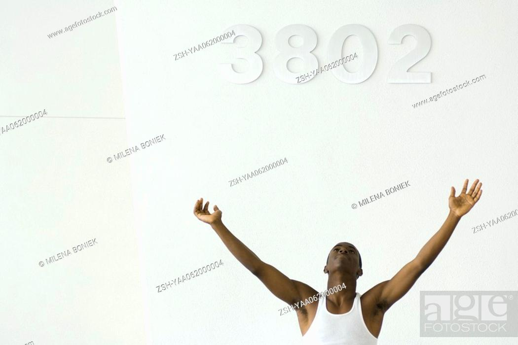 Stock Photo: Teenage boy in tank top with arms raised, looking up.