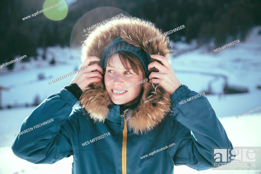 Stock Photo: Italy, Val Venosta, Slingia, smiling woman with fur hood in winter landscape.