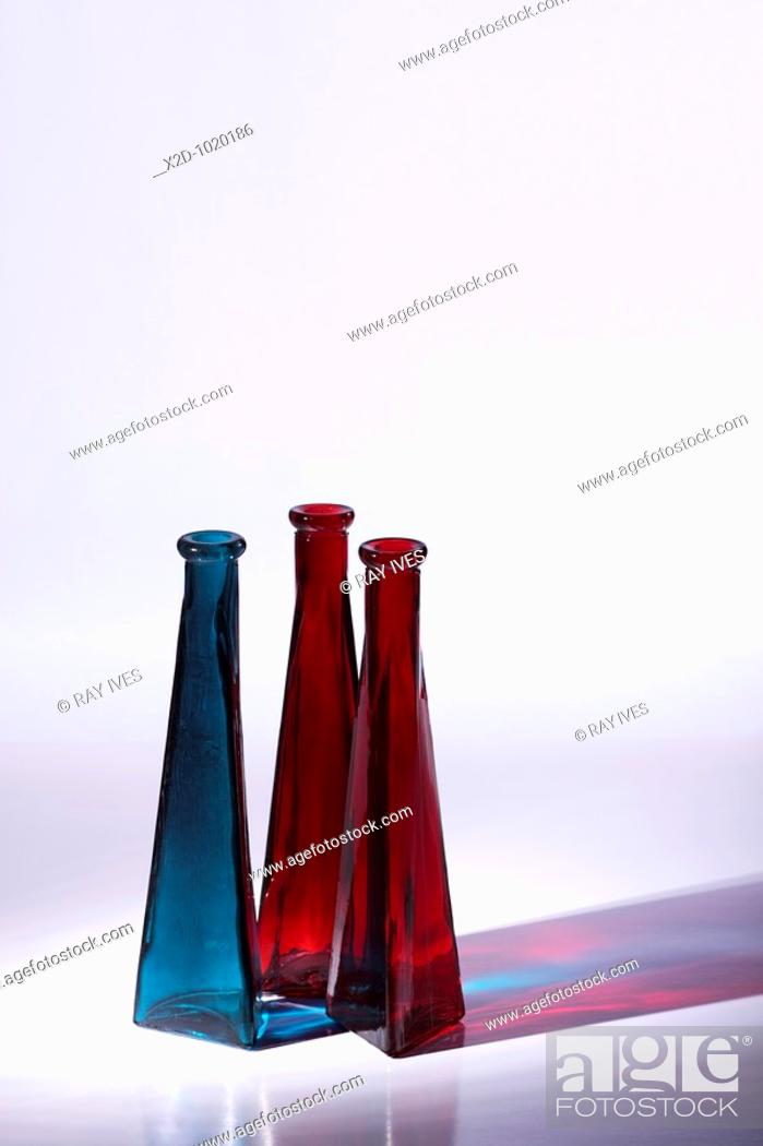 Stock Photo: Blue and red decorative glass vases  Side lit to cast colourful reflections  Isolated  Copy space.