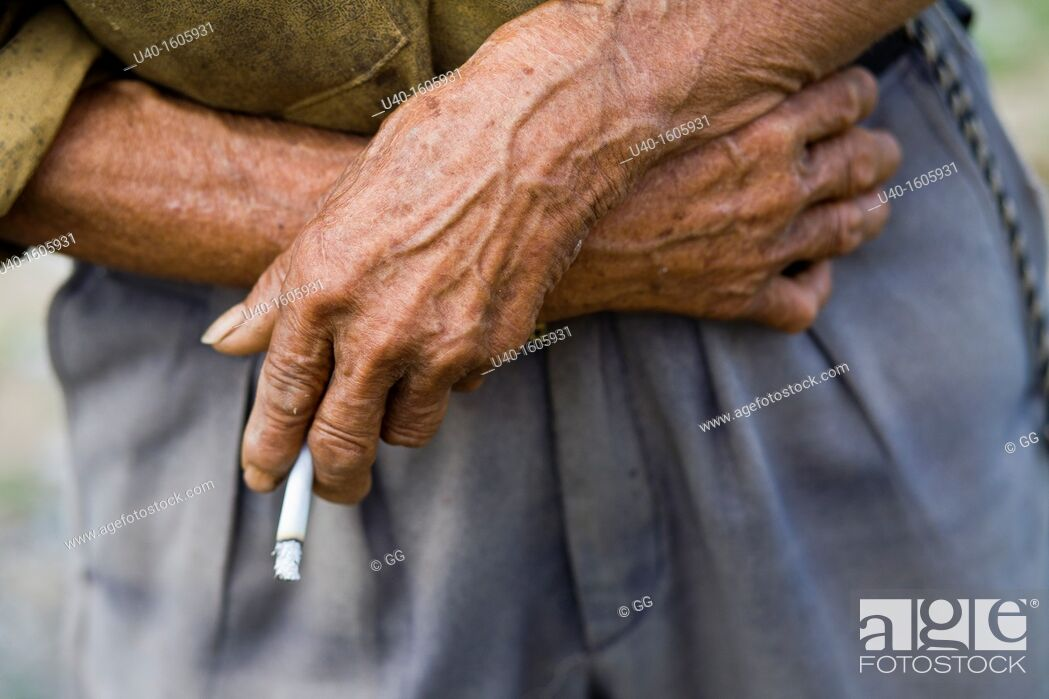 Stock Photo: Old man with cigarette in hand close up.