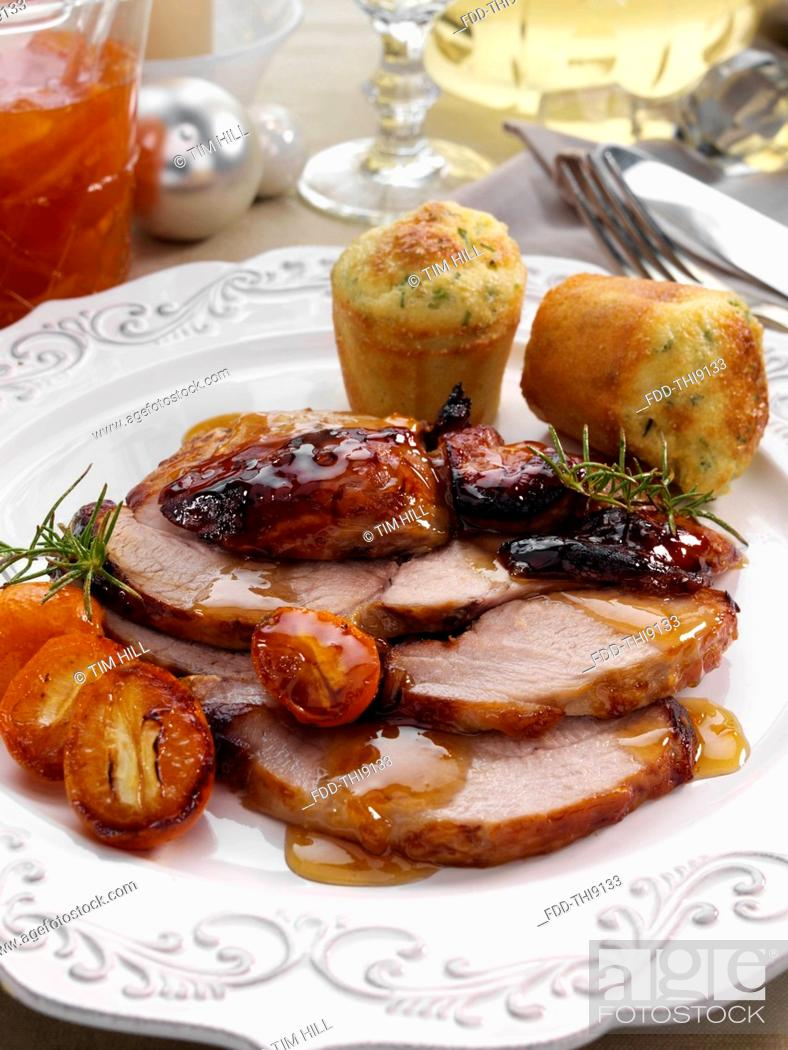 Imagen: Individual portion of leg of pork slices with kumquat marmalade glaze and cheese chive muffins main meals.