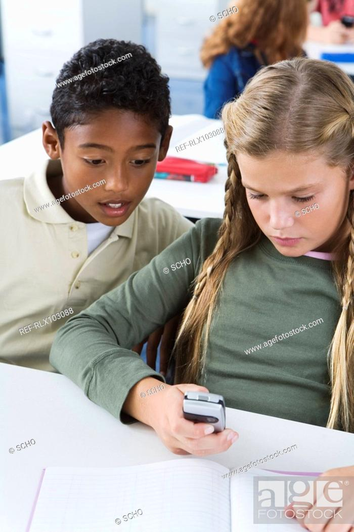 Stock Photo: School children10-13 using mobile phone in classroom, sitting looking at phone.