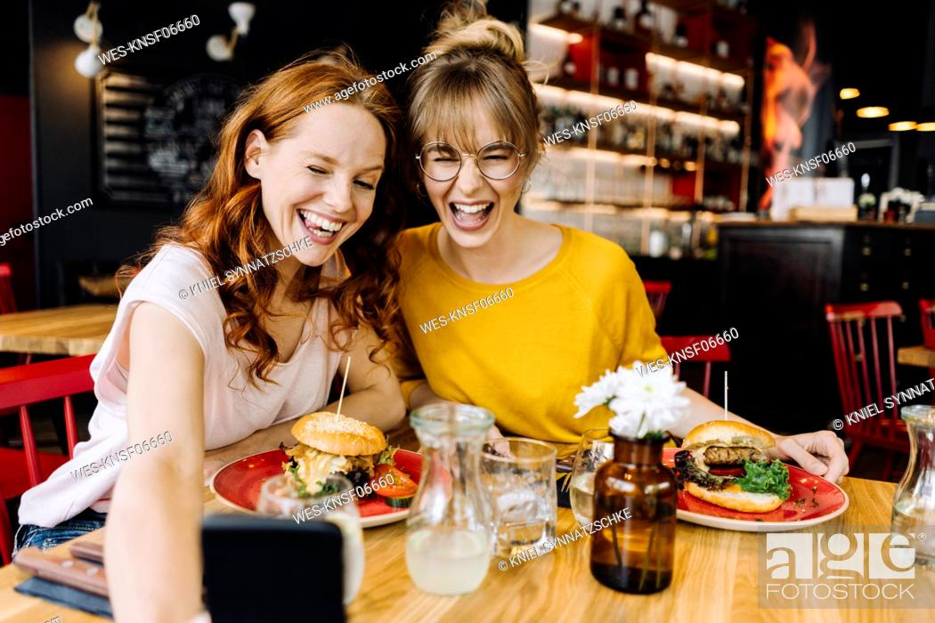 Stock Photo: Two happy female friends having burger and taking a selfie in a restaurant.