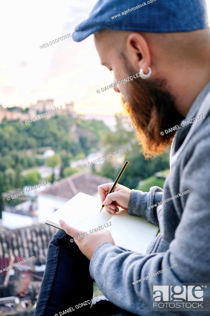 Stock Photo: Man at observation point drawing a sketch of the Alhambra, Granada, Spain.