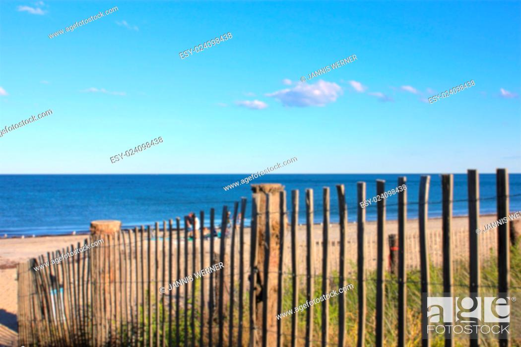 Stock Photo: Blurred Background of New England beach lying in the afternoon sun, partly seen through a fence.