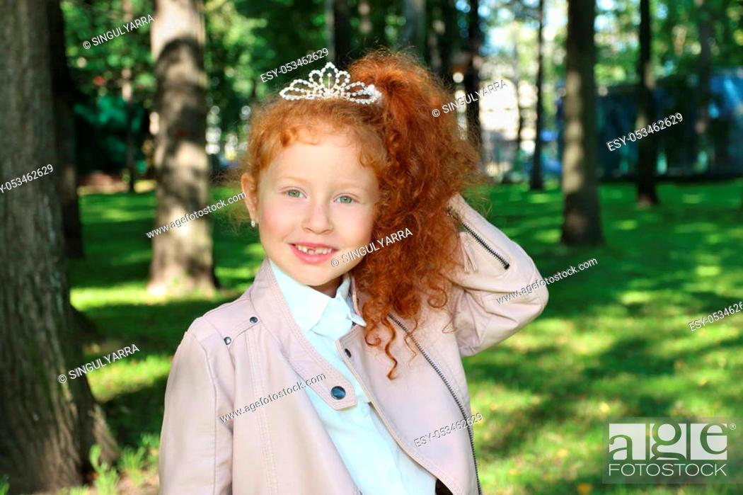 Stock Photo: Happy little girl with red hair in leather jacket poses in summer green park at sunny day.