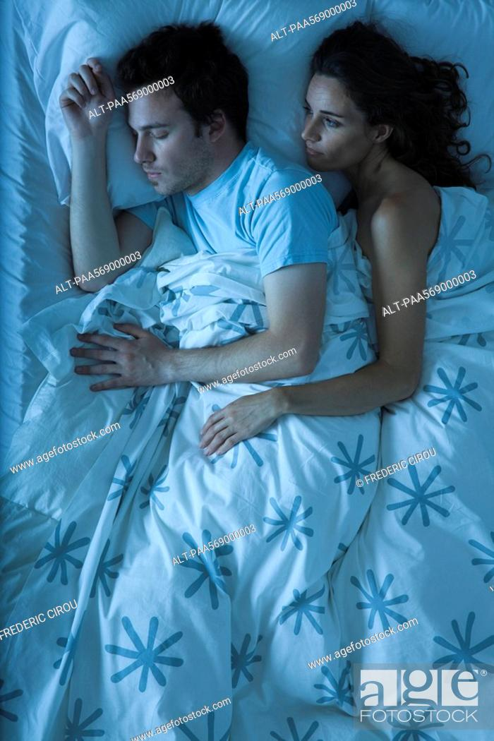 Stock Photo: Couple together in bed, woman embracing man, watching him sleep.