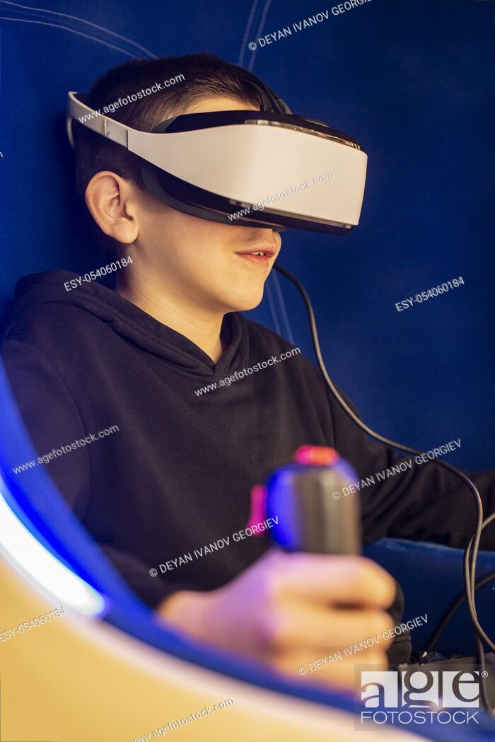 Stock Photo: Child playing game with VR glasses. Blue illuminated cabin with joysticks. Special effects. Technology, entertainment and gaming concept with virtual reality.