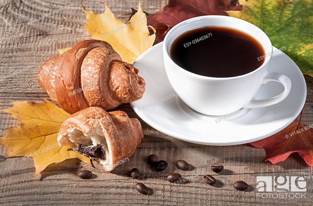 Stock Photo: Coffee with a croissant on a wooden table. Grains of coffee and maple leaves on the table.