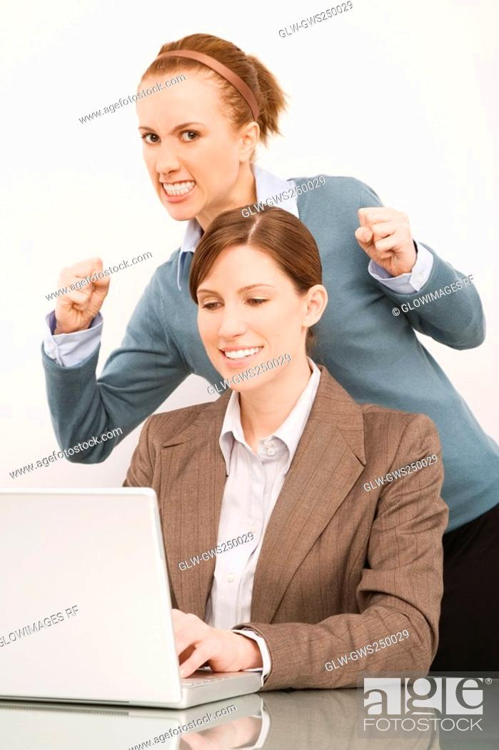 Stock Photo: Businesswoman working on a laptop with her colleague clenching teeth behind her.