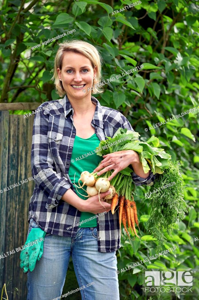 Stock Photo: Woman in the garden with carrots.