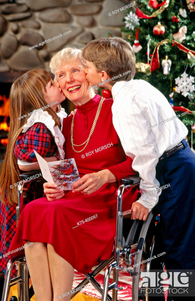 Stock Photo: Children giving Grandma Christmas kisses.