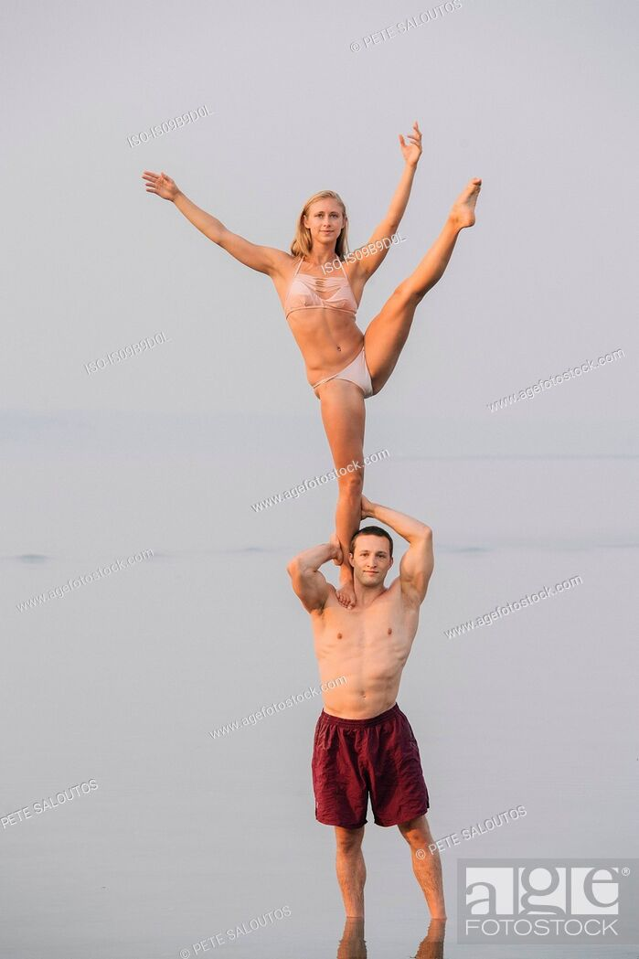 Imagen: Young couple on beach, woman balancing on one leg, on man's shoulder.