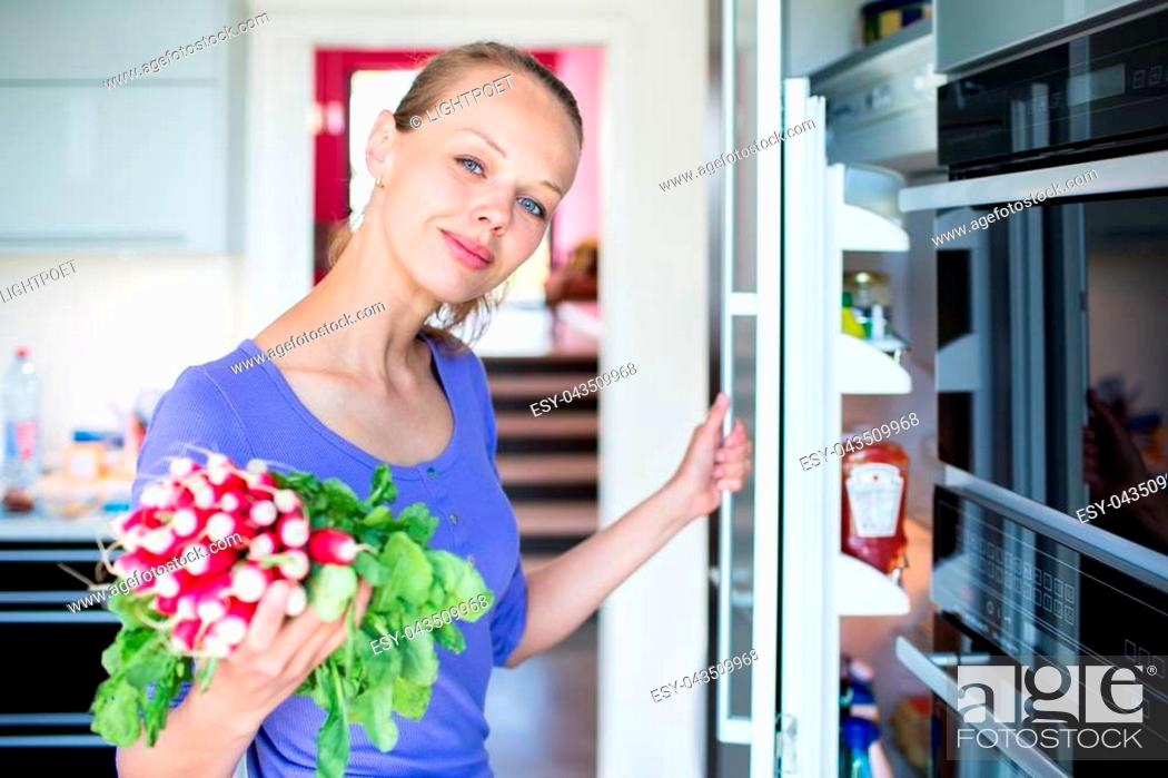 Stock Photo: Pretty, young woman taking fresh vegetables from her fridge - being on a gluten free vegan diet does not seem to be a problem for her (shallow DOF; color toned.