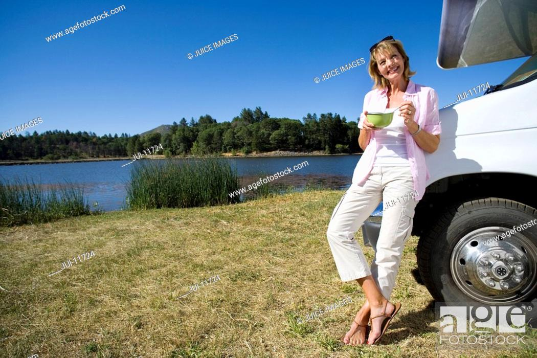 Stock Photo: Woman with bowl by motor home and lake, smiling, portrait, low angle view.