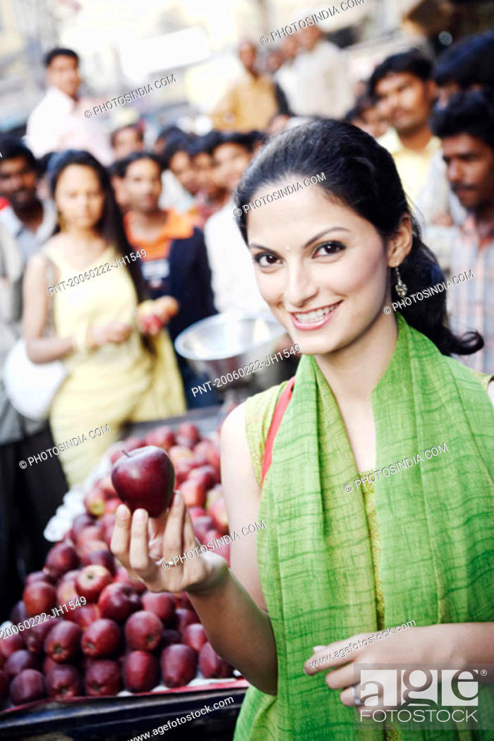 Stock Photo: Portrait of a young woman holding an apple.