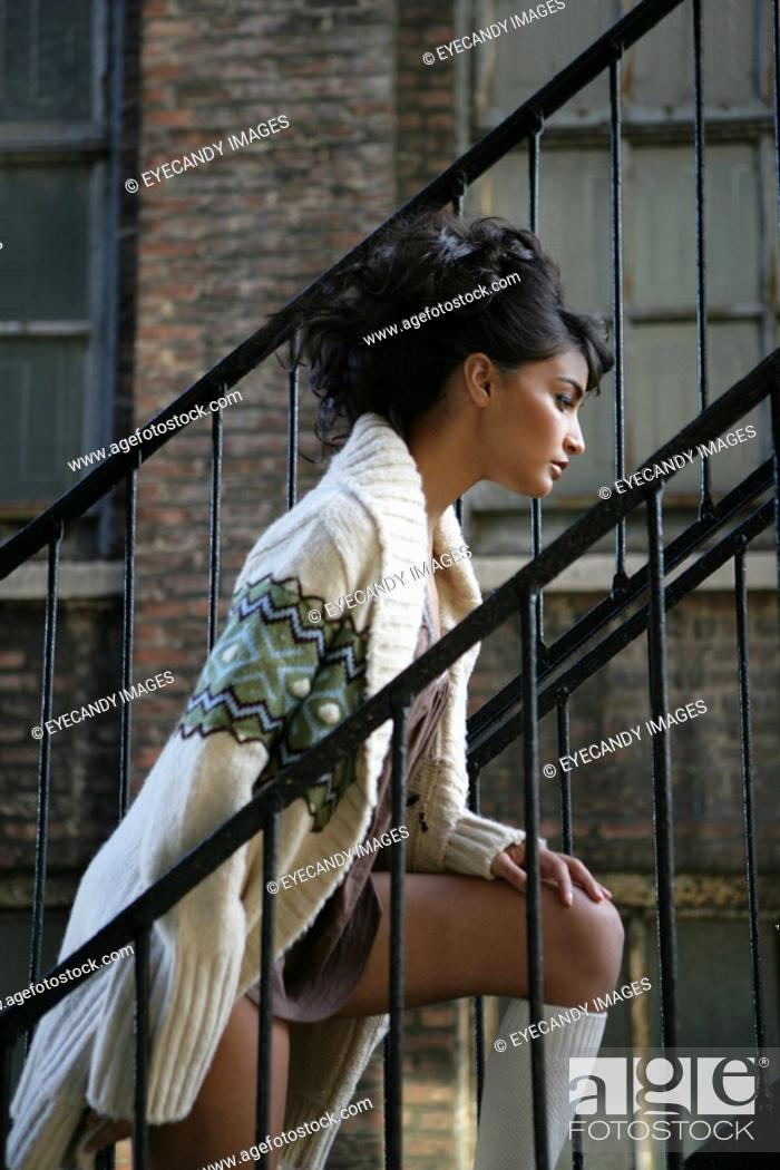 Stock Photo: Young stylish woman walking up fire escape.