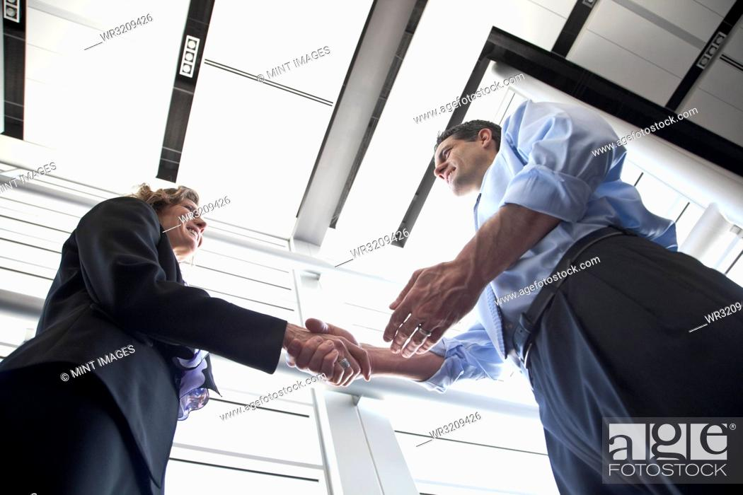 Stock Photo: Businessman and woman meeting in the lobby of a conference centre.