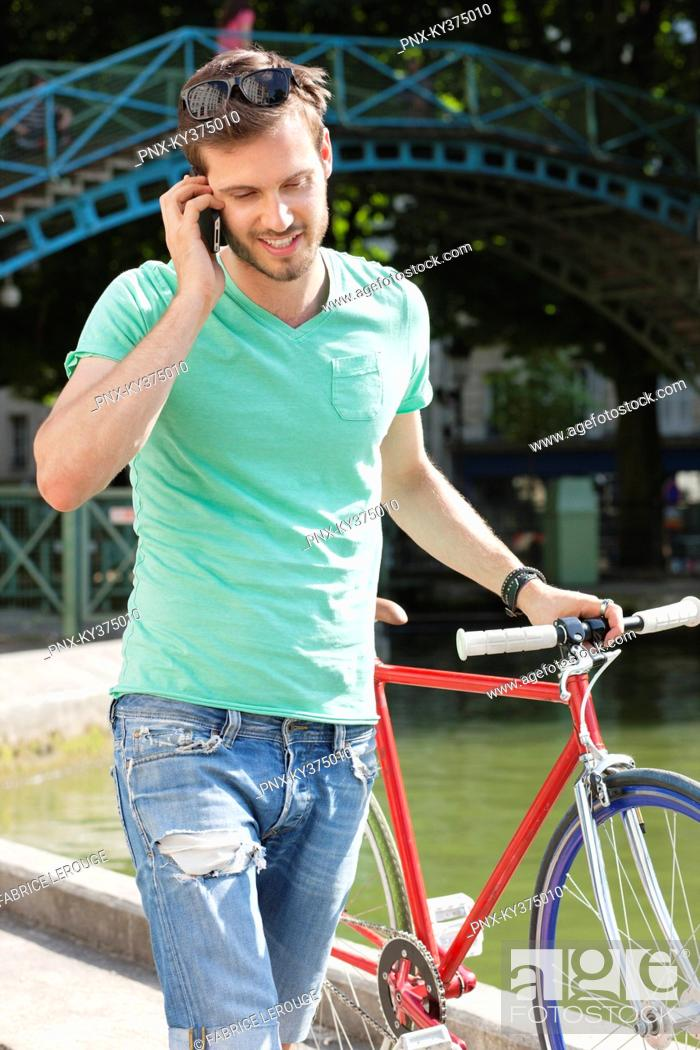 Stock Photo: Man walking with a bicycle and talking on a mobile phone, Paris, Ile-de-France, France.