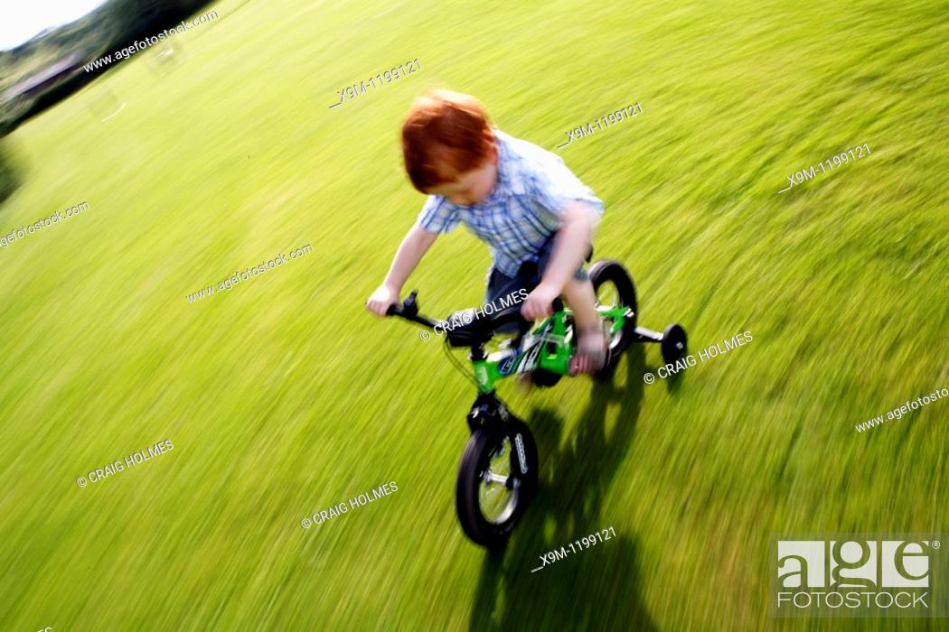 Stock Photo: Boy cycling on a bike with stabilisers in Birmingham Park.