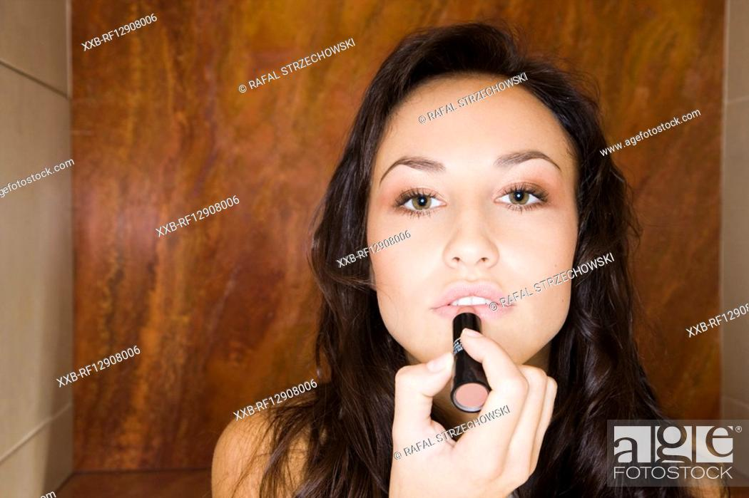 Stock Photo: young woman using lipstick.