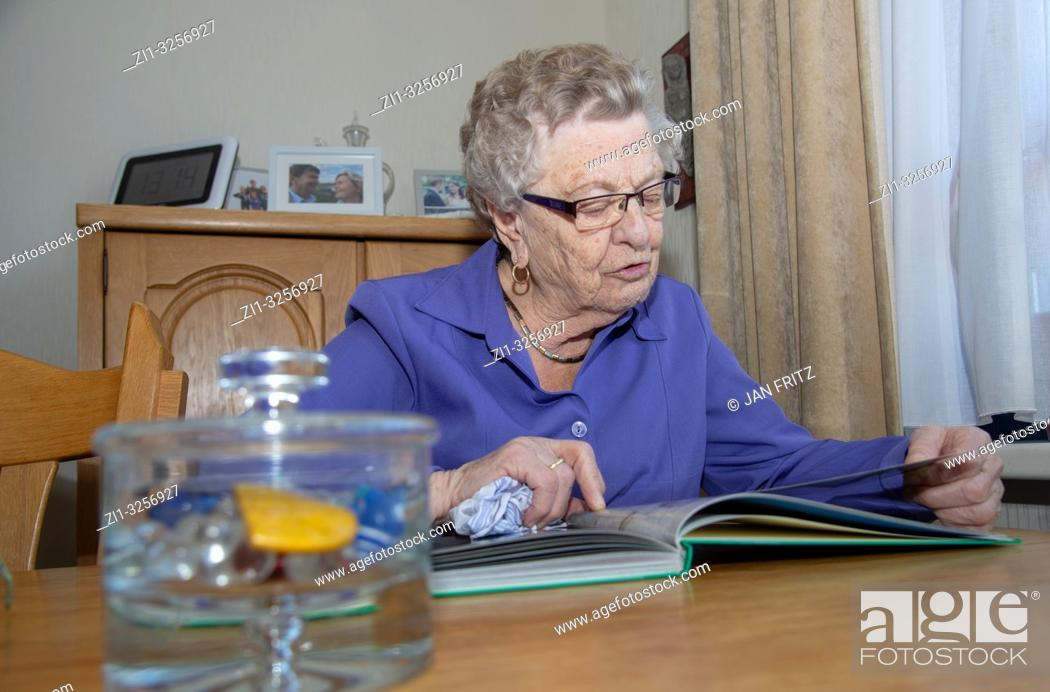 Stock Photo: old woman reading book.
