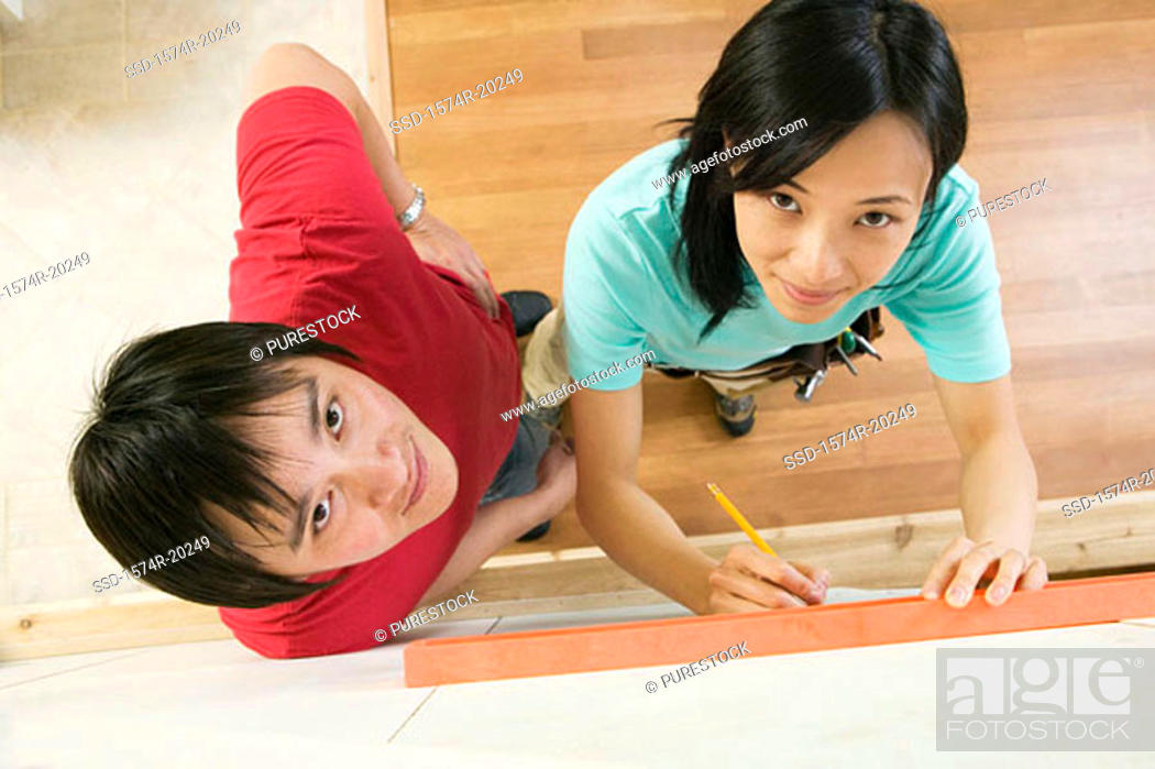 Stock Photo: High angle view of a young woman using a spirit level to mark on a wall with a young man standing beside her.