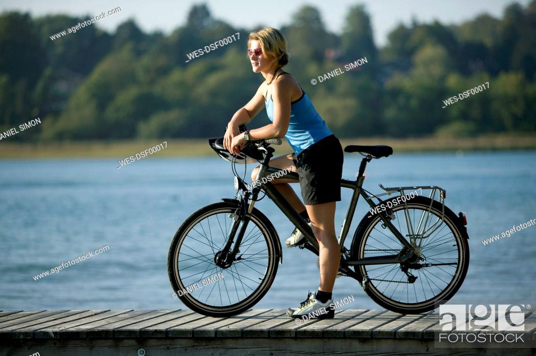Stock Photo: Germany, Bavaria, Tegernsee, Woman with mountain bike on landing stage.