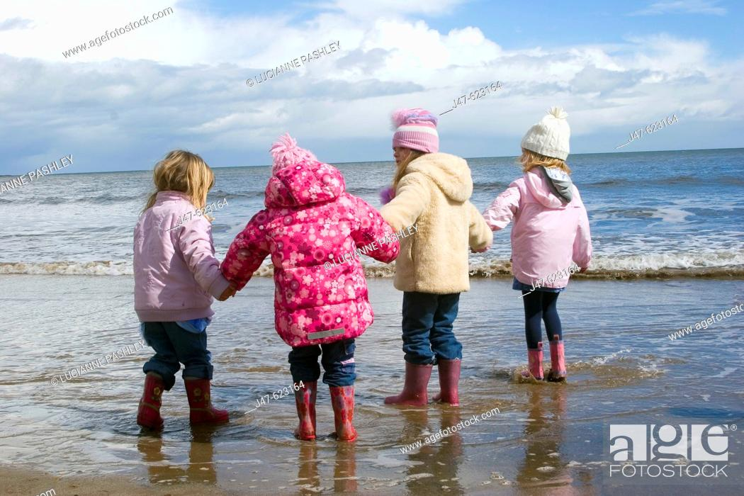 Stock Photo: Group of 4, 4 year old girls standing on the seashore all in a row holding hands, dressed in winter clothing.