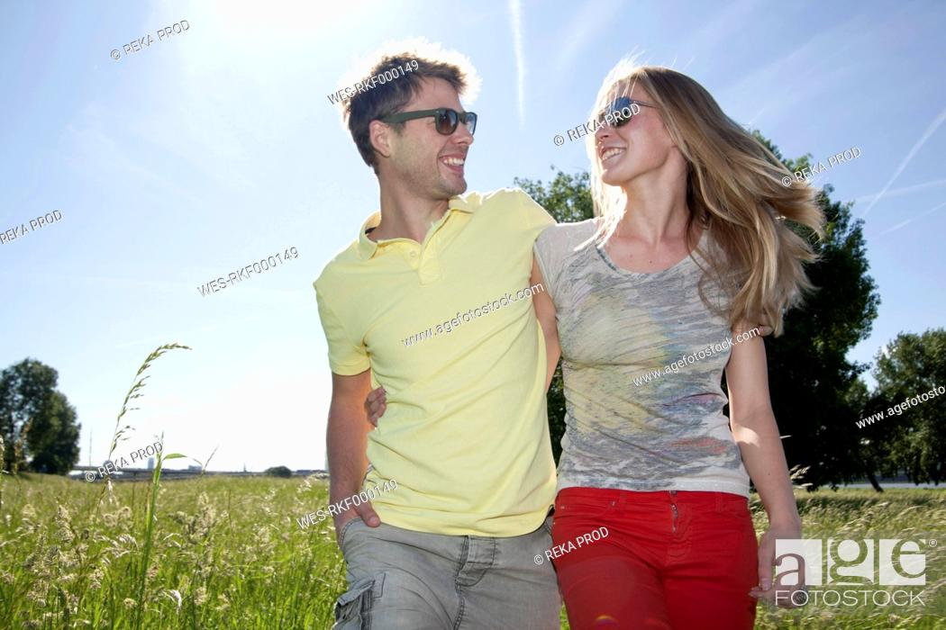 Stock Photo: Germany, North Rhine Westphalia, Duesseldorf, Couple walking in grass, smiling.