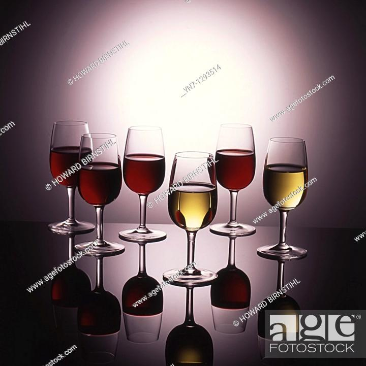 Stock Photo: Display of wine in glasses on glowing background with reflections.