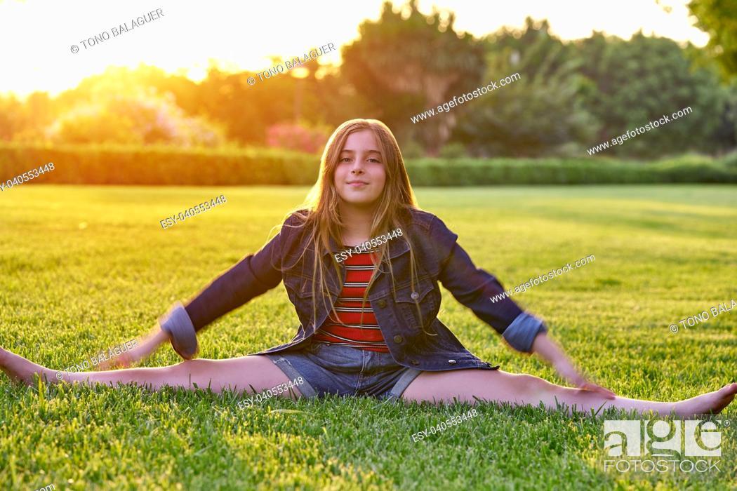 Photo de stock: Blond kid girl splitting legs at sunset park outdoor.