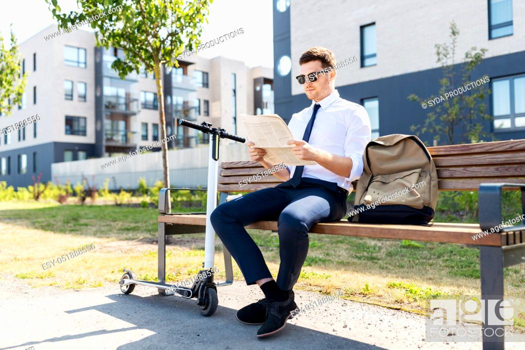 Stock Photo: businessman with scooter reading newspaper in city.