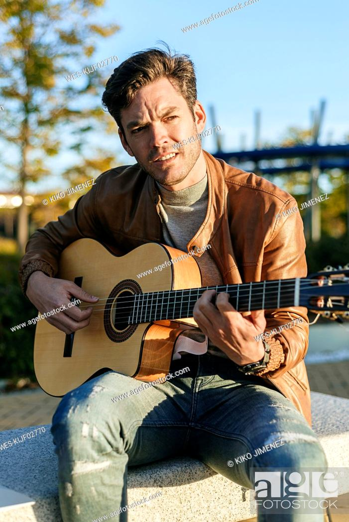 Imagen: Portrait of man playing guitar outdoors.