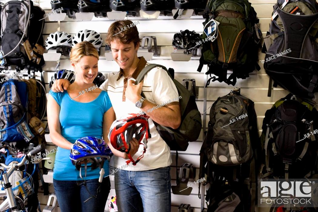 Stock Photo: Young couple looking at bicycle helmets in shop.